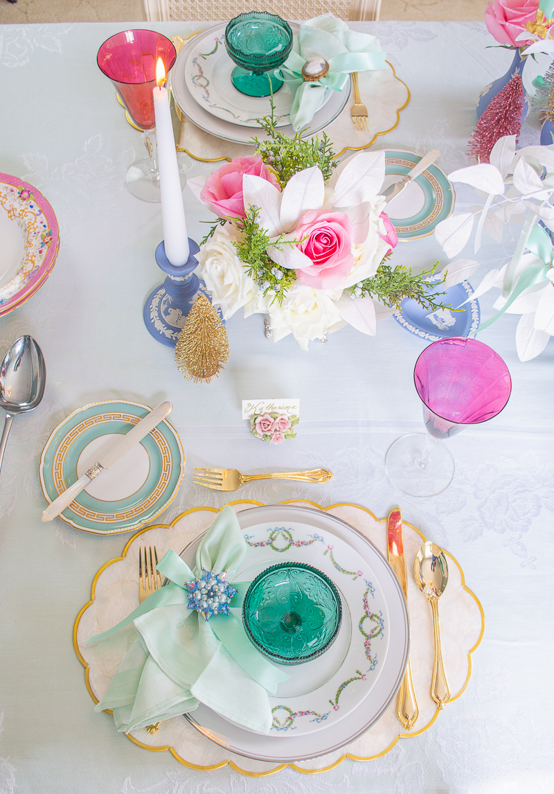 top view of place setting on Christmas table featuring antique German china, tiara sherbet glassware, capiz shell placemats, and a vintage brooch napkin ring