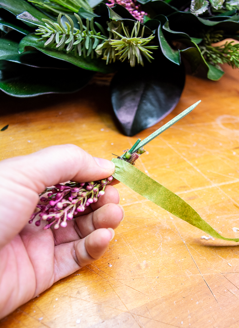 Creating a pick with the pink heather blooms using a wooden floral pick with wire and floral tape