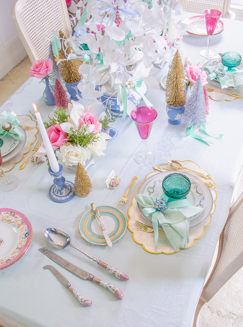 Over head view of Jasperware and vintage jewelry on a fanciful and bright pastel holiday tablescape.