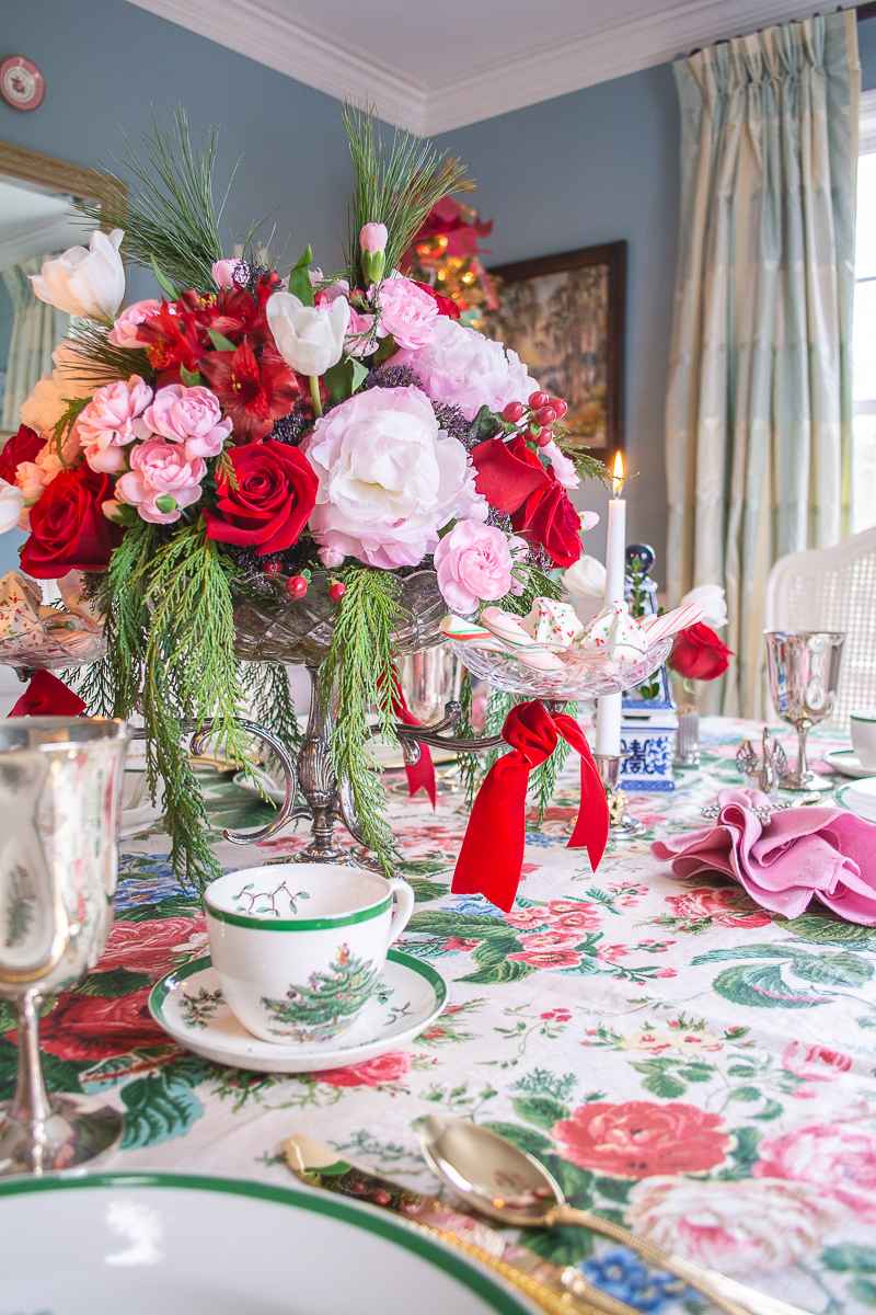 Silver and crystal epergne with red roses and pink peonies create drama on this grandmillennial Christmas tablescape