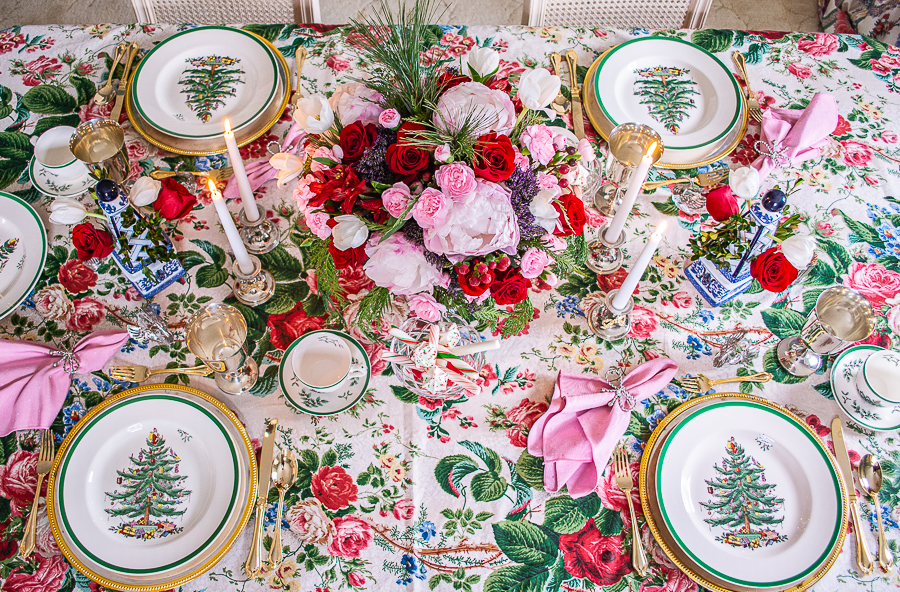 horizontal top view of grandmillennial holiday tablescape with classic Christmas china, red and pink florals, and a chintz tablecloth
