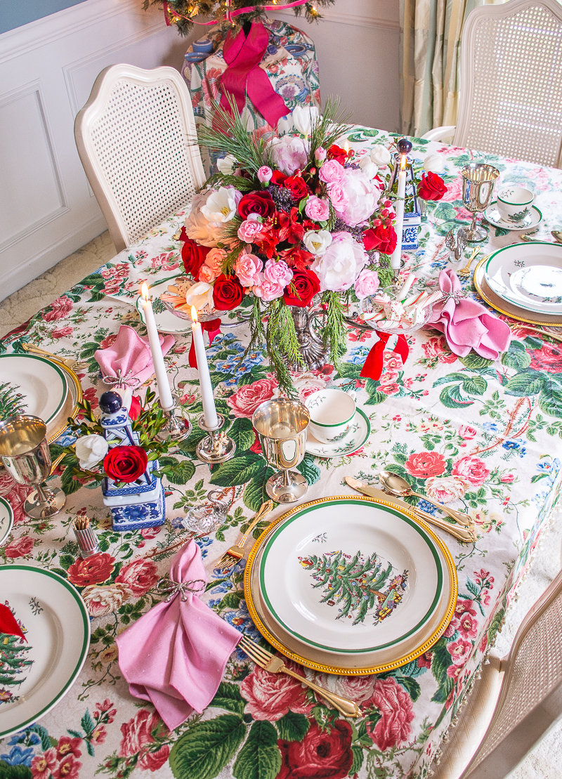 A grandmillennial Christmas table with vintage chintz tablecloth, heirloom silver, Spode Christmas tree china, and rose, peony floral centerpiece