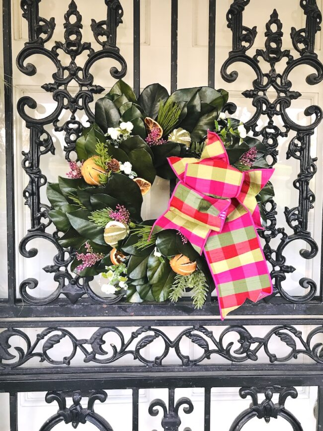 Preserved magnolia wreath with citrus and evergreen and pink and green plaid bow