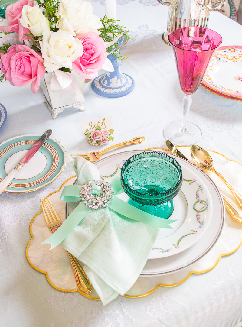 A sparkling vintage brooch tied with mint green bow encircles a linen napkin at this pastel place setting