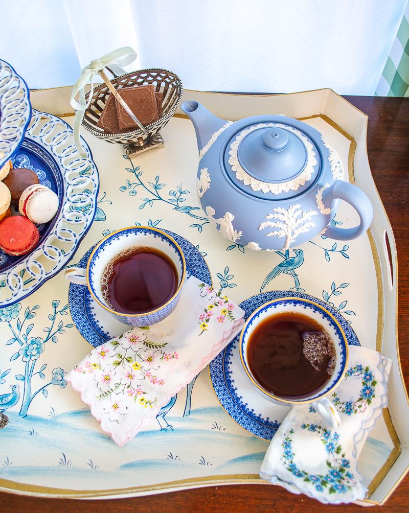 Pair of Blue Lace Mottahedeh tea cups filled with black tea and Wedgwood teapot on blue and white tole tray