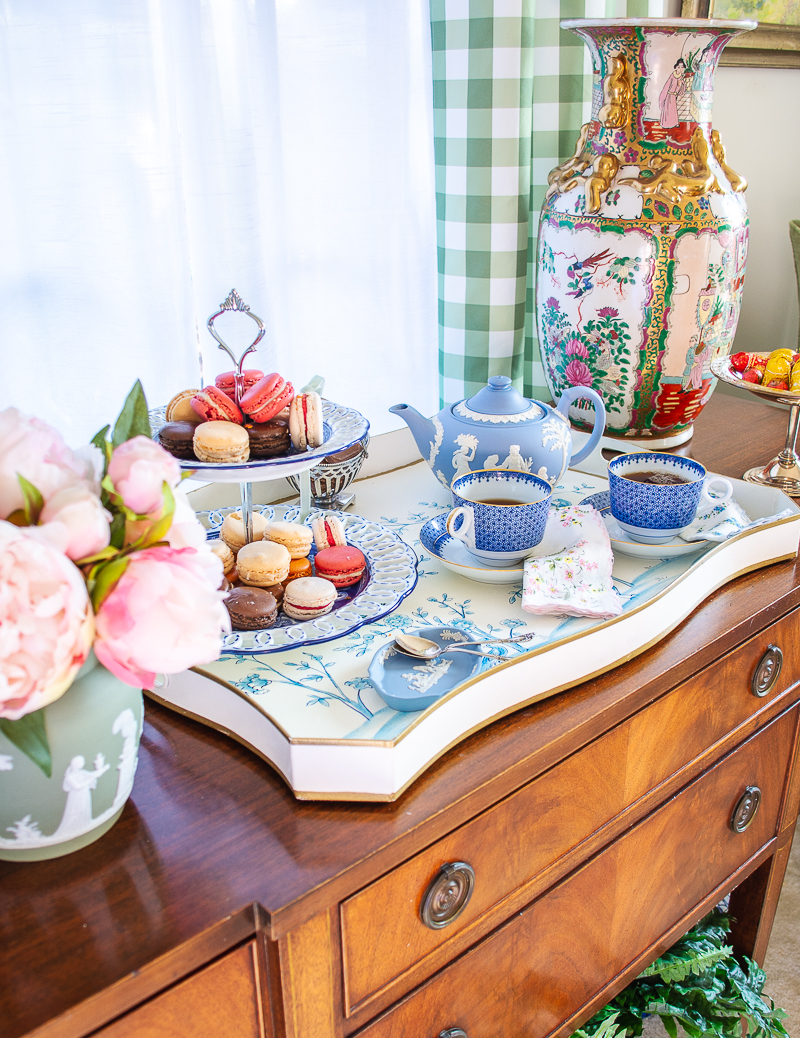On sideboard Blue and white winter tea set up with tole tray, Wedgwood Jasperware teapot, Mottahedeh blue lace teacups, macarons, and pink peonies