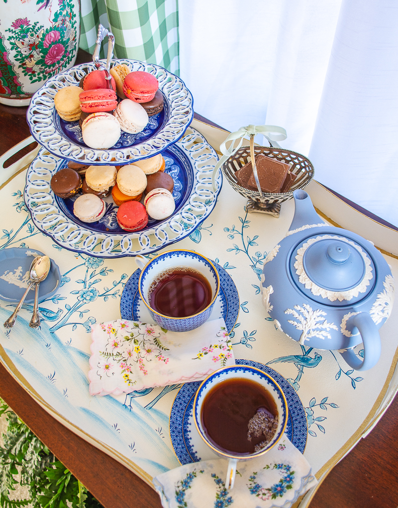 delightful winter tea setup with blue and white teacups, Wedgwood teapot, macrons, chocolate biscuits, and black tea