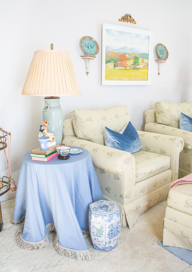 For a soothing palette mix pale shades of green and blue like what's done here with these green floral armchairs, celadon lamps, and blue skirted tables.