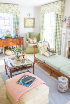 My grandmillennial living room decorated in green, white, blue, and pink with chintz and gingham window treatments, wicker furniture, and colorful accessories.