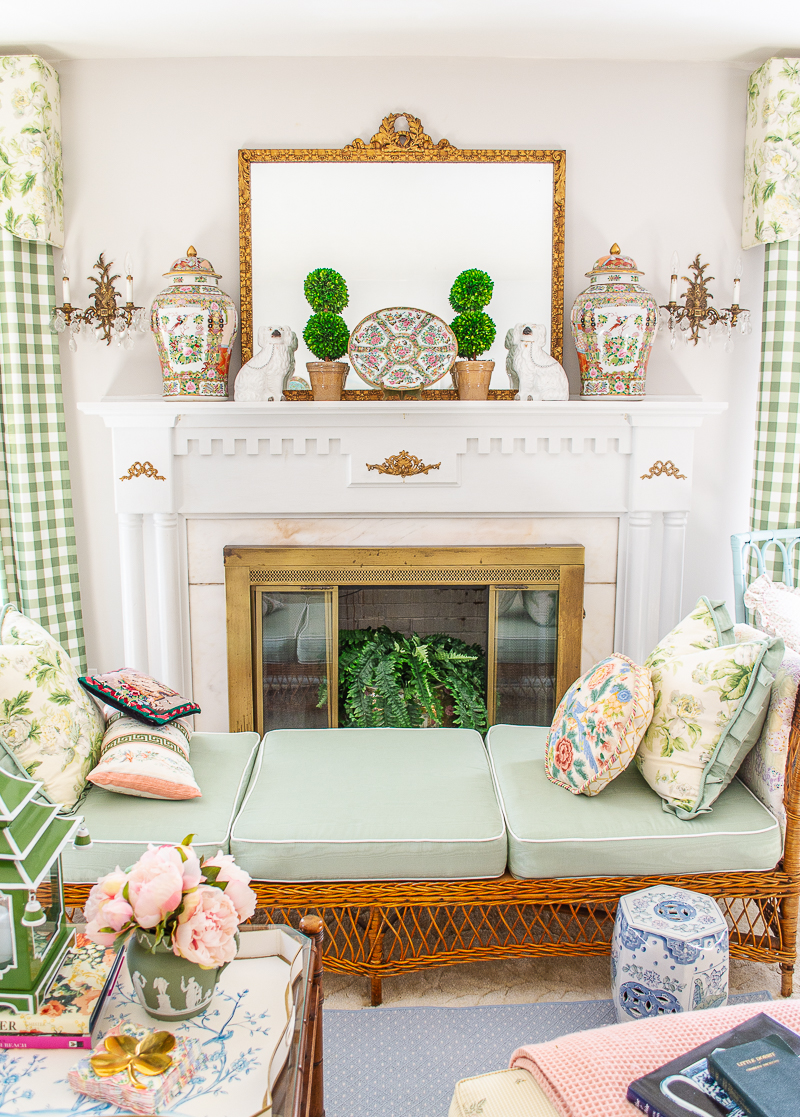 Fireplace with gilt mirror, boxwood topiaries, Rose Medallion temple jars, and Staffordshire spaniels. Wicker day bed sits in front with green cushions.