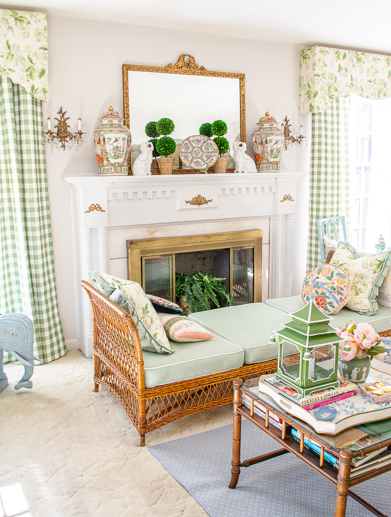 The fireplace in my grandmillennial living room decorated in green, chintz, gingham, and wicker showcases how to decorate with green hues.