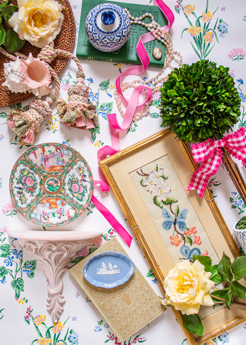 Flatlay with grandmillennial decor showcasing how to decorate with pink - boxwood topiary, pink gingham bow, botanical florals, rose medallion, wicker, Wedgwood, and needlepoint