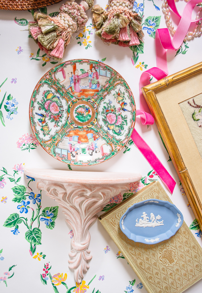 Flatlay with botanical wallpaper and rose medallion plate above ceramic wall shelf - decorate with pink