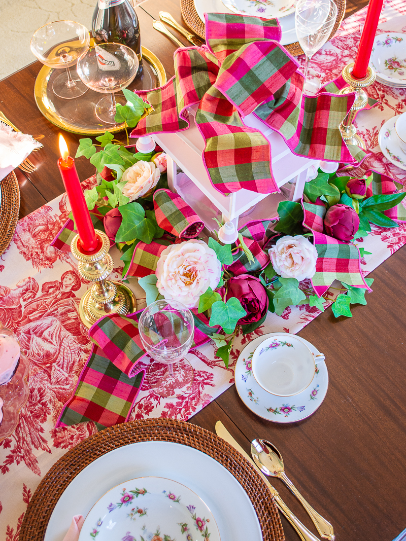 Floral centerpiece with pagoda and ribbon, featuring faux camellias, pink peonies, and ivy.