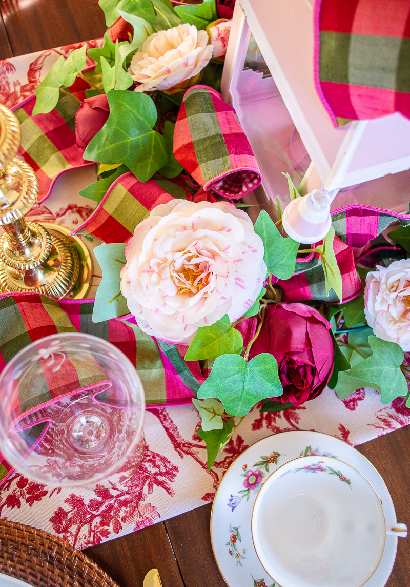 Faux pink camellia nestled in centerpiece wreath on toile tablescape