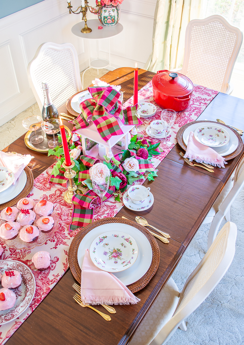 A love & toil tablescape for Valentine's day, mixing red toile runner with faux floral centerpiece, pink pagoda lantern, and Dresdenia china