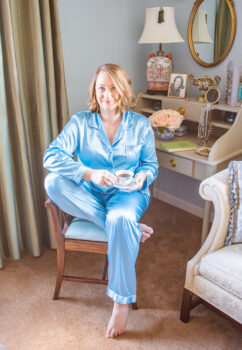Katherine sitting on vanity bench in pretty loungewear of matching set of aqua pajamas