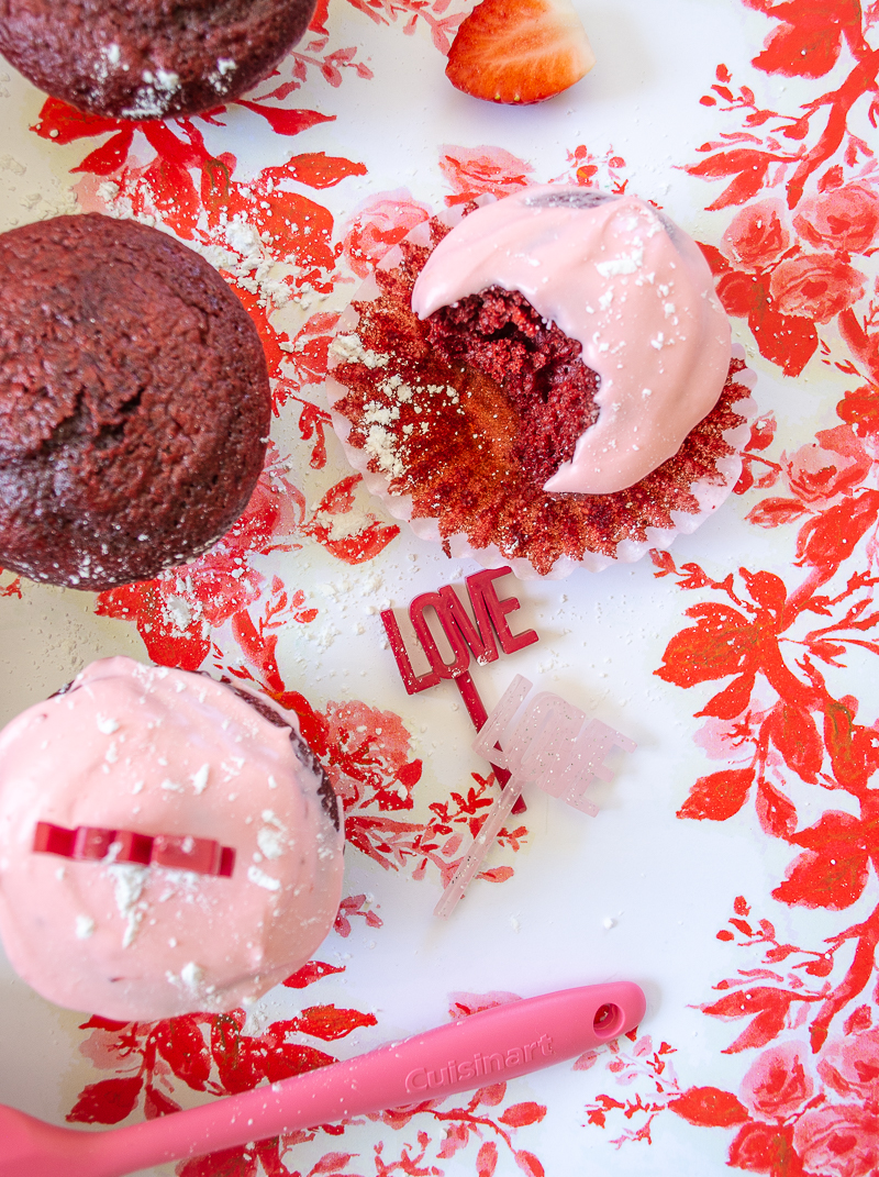 Red velvet cupcakes with strawberry cream cheese frosting on red and pink floral paper