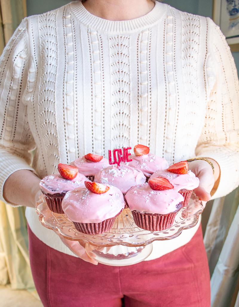 Katherine holding plate of red velvet cupcakes with strawberry cream cheese frosting