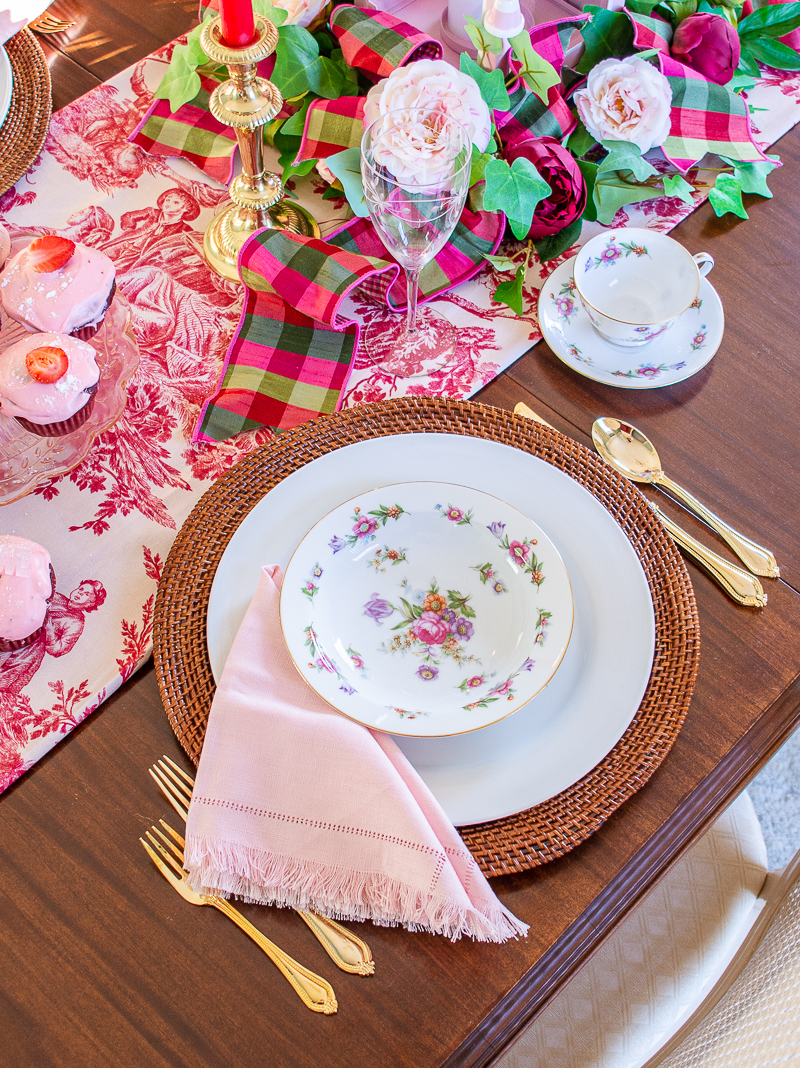 Dresdenia china floral design with roses and tulips set on white plate with rattan charger and pink napkin