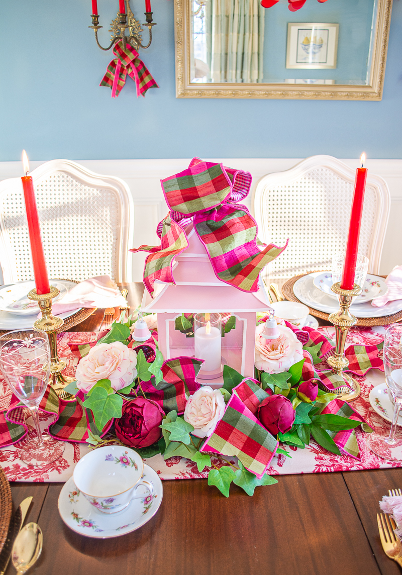 Pink pagoda lantern nestled in faux floral wreath with ivy, peonies, and camellias on toile tablescape