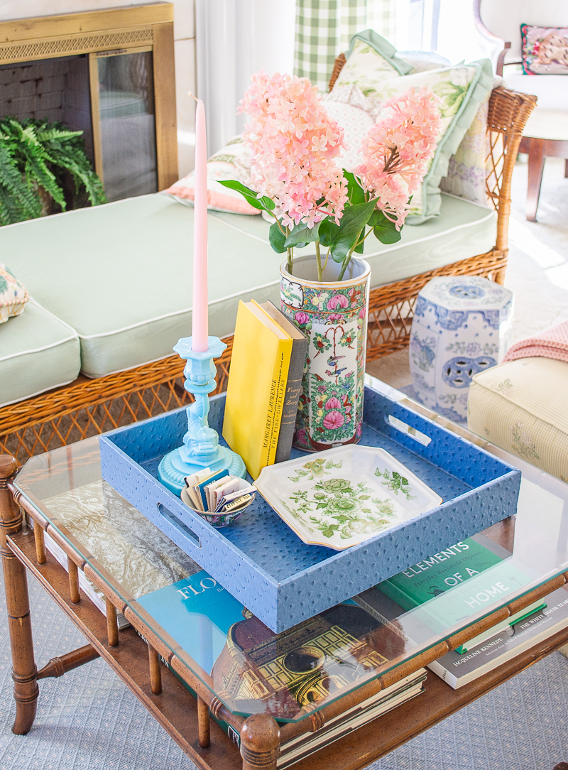 Coffee table style in Chinoiserie chic with bright happy colors using blue ostrich tray, rose canton vase, aqua opaline candlestick, and books