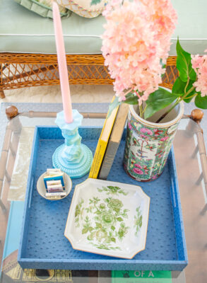 top down view of chinoiserie coffee table with blue tray, dolphin candlestick, and rose canton vase