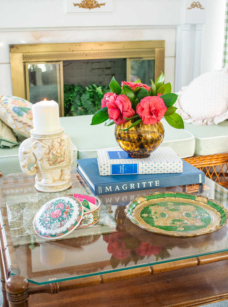 coffee table styled with eclectic decor, including a green Florentine tray, rose canton box, elephant candle pillar, and tortoiseshell vase