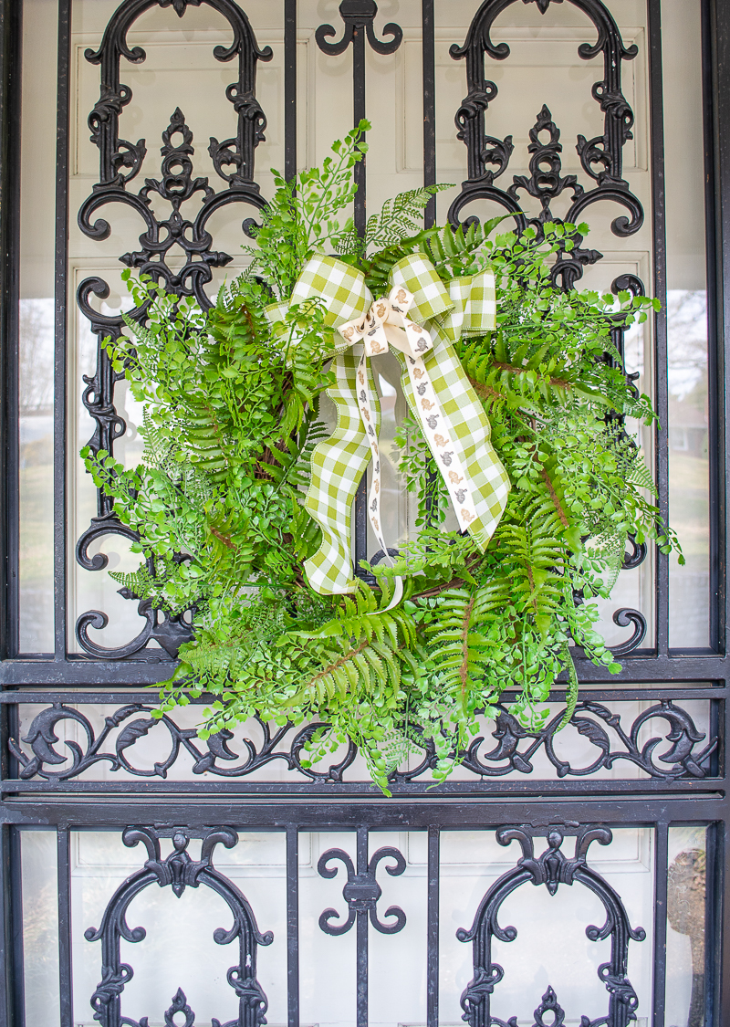 Add a little touch of spring with a faux fern wreath on black wrought iron front door with gingham and bunny ribbon bow