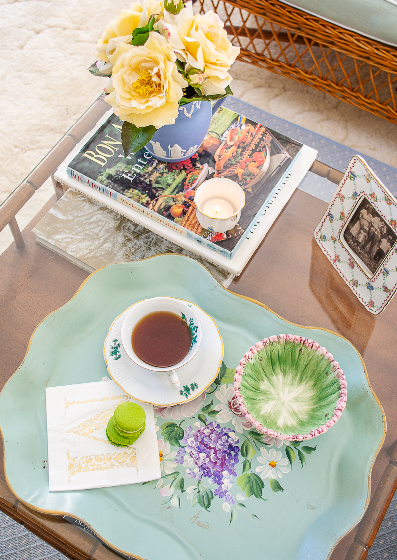 Top view of grandmillennial coffee table styled with tole tray, yellow roses, Wedgwood, Herend, and family photo
