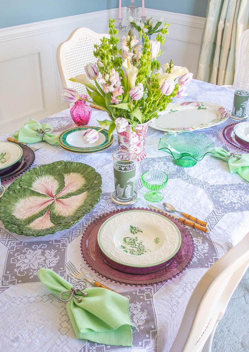 Angle view of springtime table in green and white with Wedgwood Patrician bowls and purple glass chargers