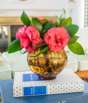 Tortoise shell glass vase filled with pink camellias