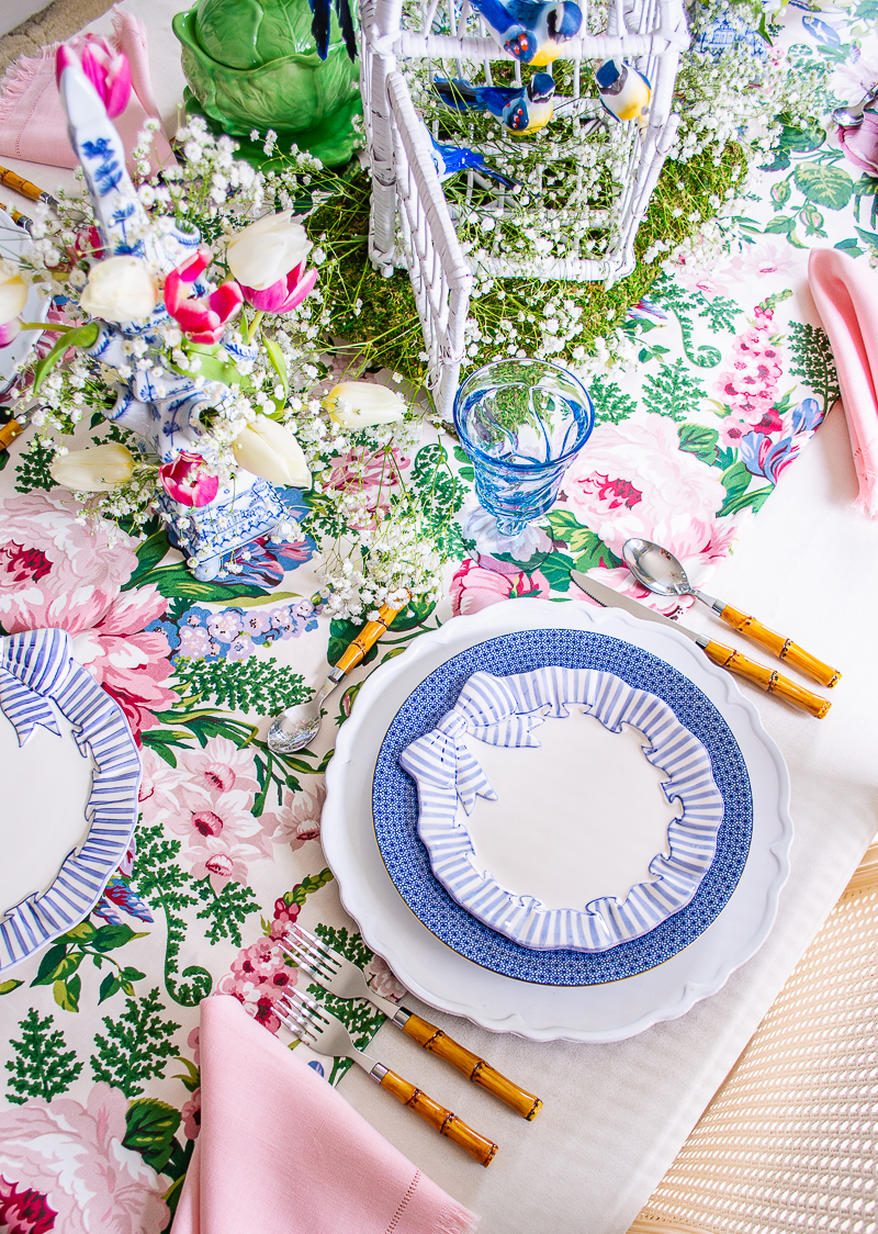 angled view of place setting with blue and white tulipiere and wicker bird cage centerpiece