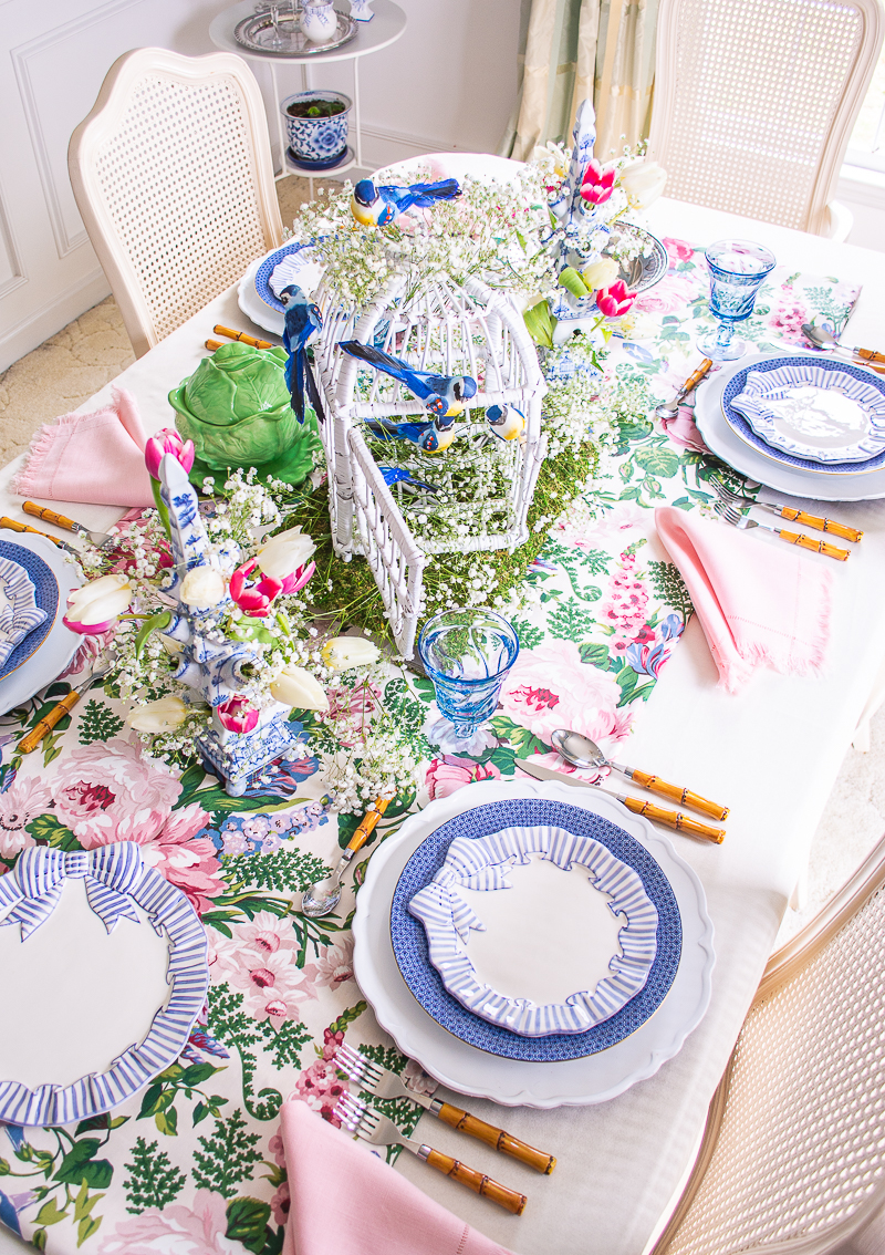 White wicker bird cage with blue songbirds centers this spring table set with blue bow plates and Mottahedeh china