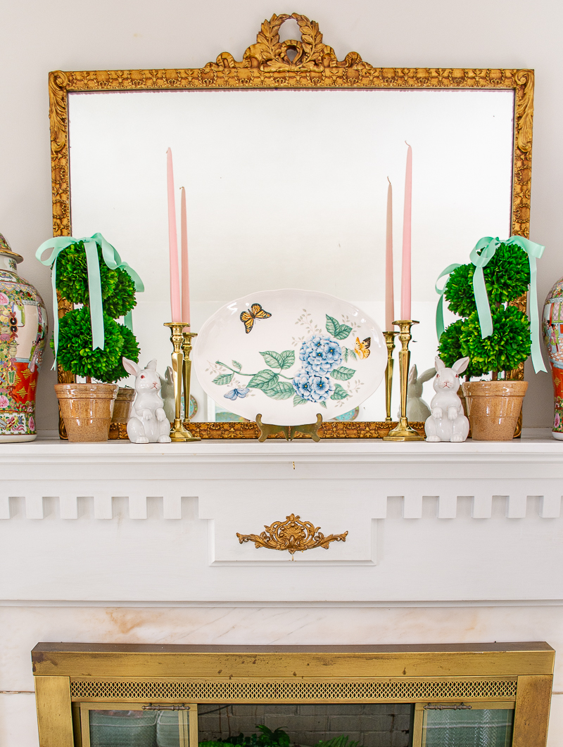 Spring mantel with boxwood topiaries and mint green bows, butterfly meadow platter, and white bunnies