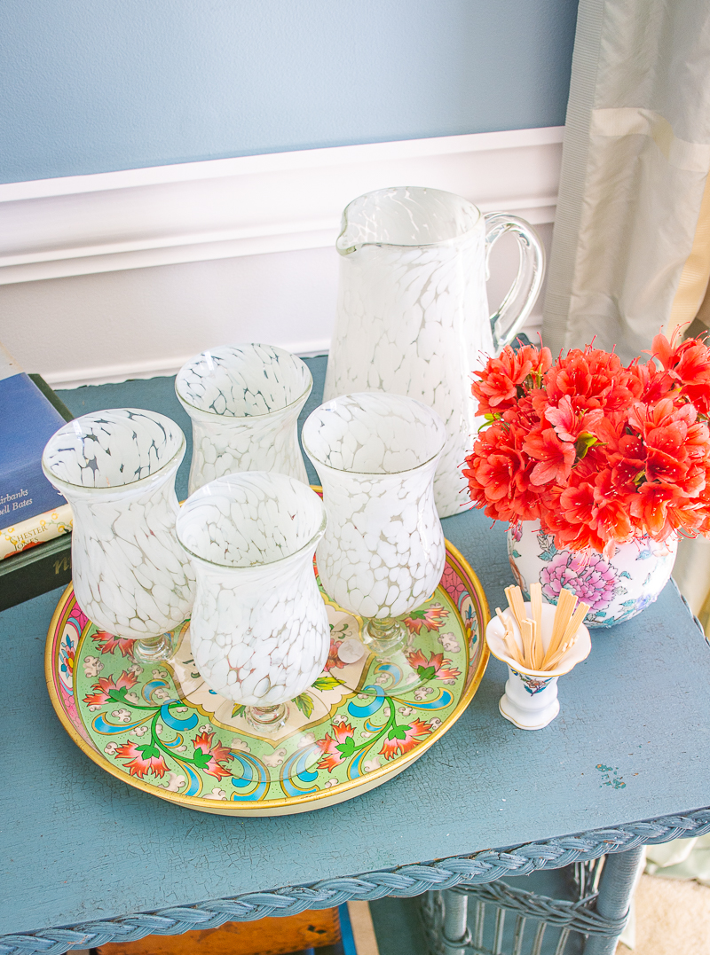 White glass pitcher and glass set on Daher colorful tin tray