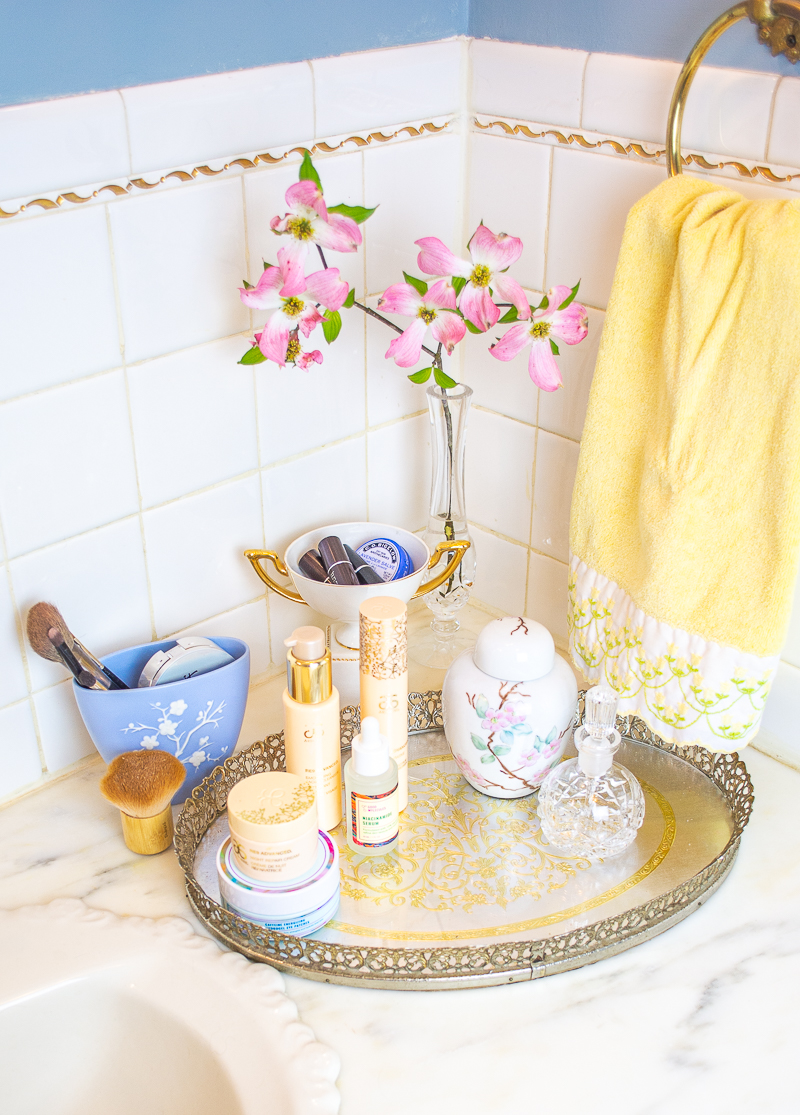 A glamorous tray on the bathroom vanity corrals makeup and skin care products