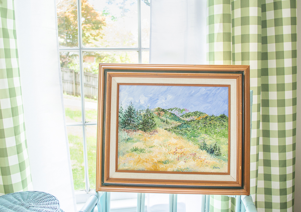 Mountain landscape painting propped in front of window - artwork inspired my deeper thinking about going green