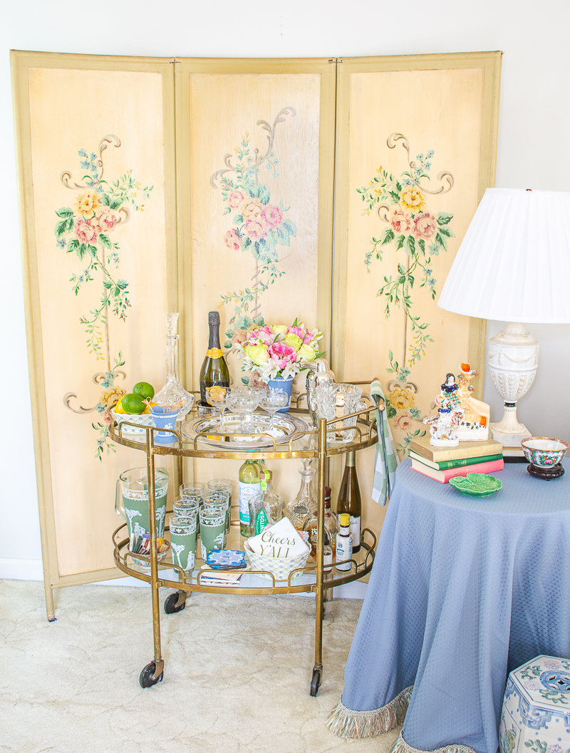 View of Katherine's vintage brass bar cart in front of floral screen in formal living room