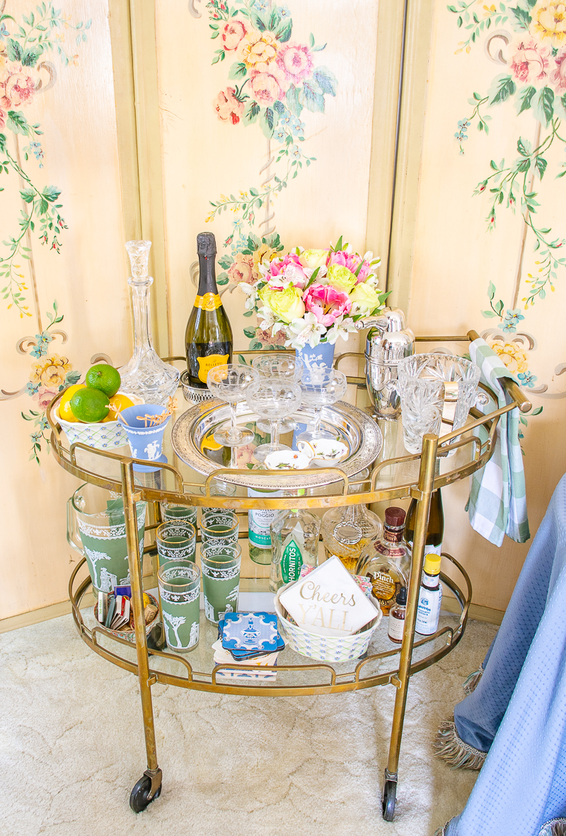 view of Katherine's vintage brass bar cart decorated in chic bar ware with Wedgwood, Herend, and florals