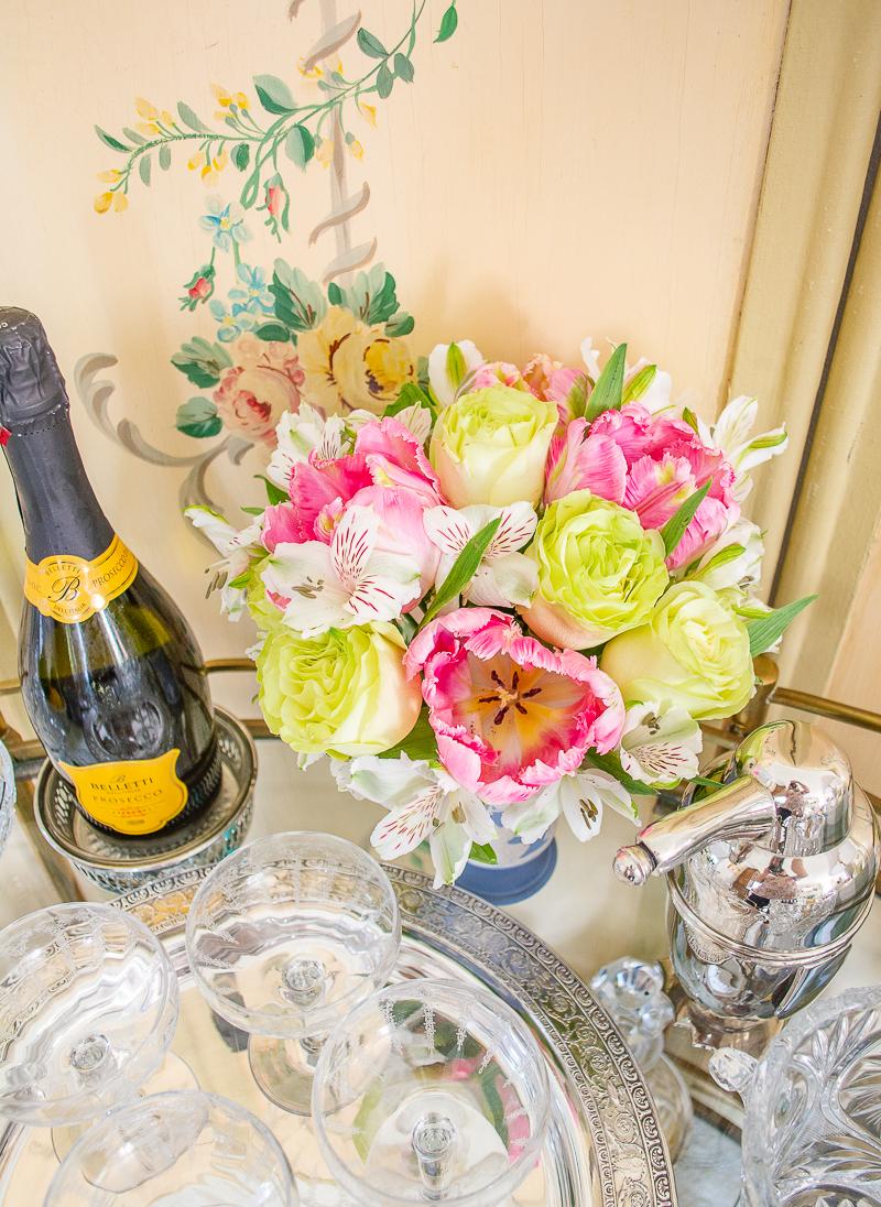 Floral arrangement of pink tulips and roses in Wedgwood Jasperware vase on bar cart