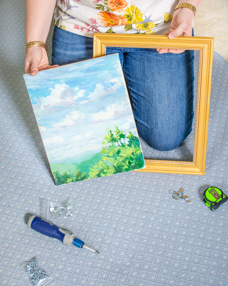 Katherine holds landscape painting and gold frame ready to show how to frame a canvas painting