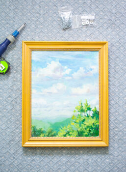 How to frame a painting with offset clips - finished landscape painting in gold frame.