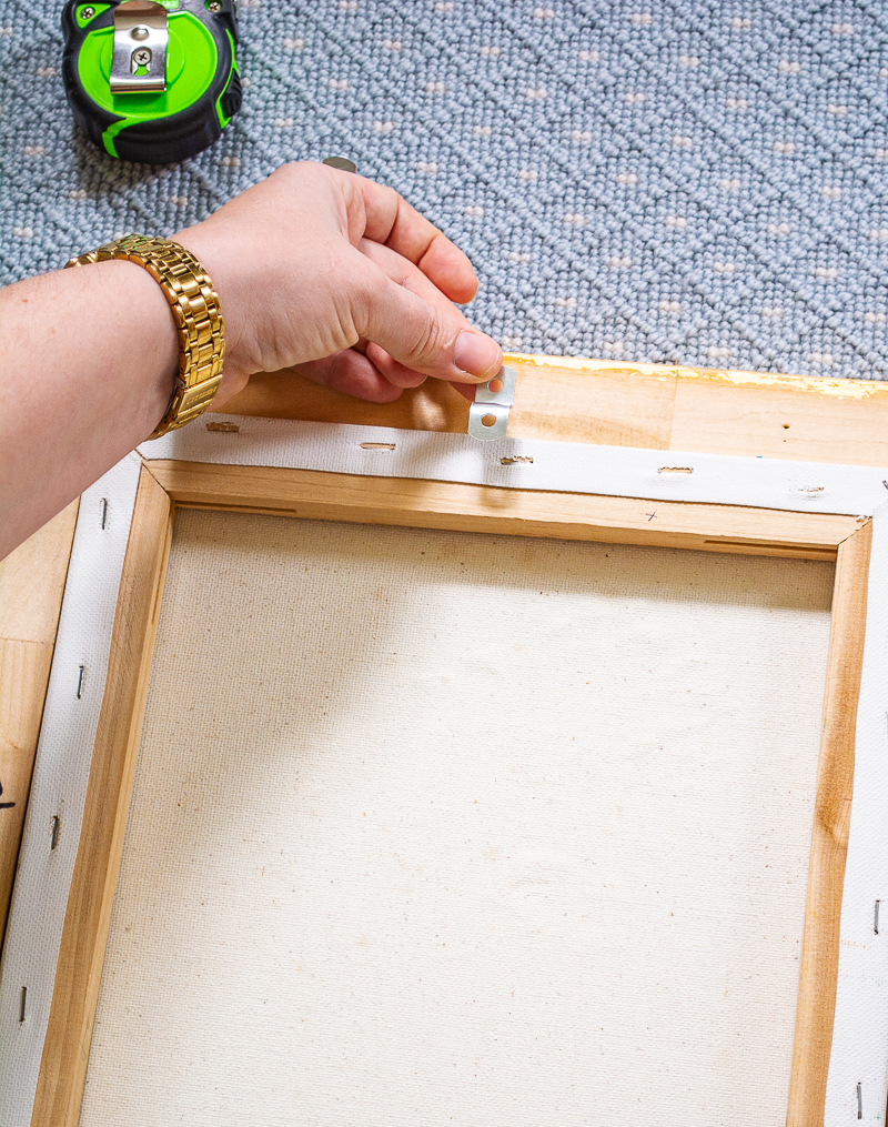 How to frame a painting with offset clips and a back-loading frame: here Katherine places a clip at the top of the painting and frame.