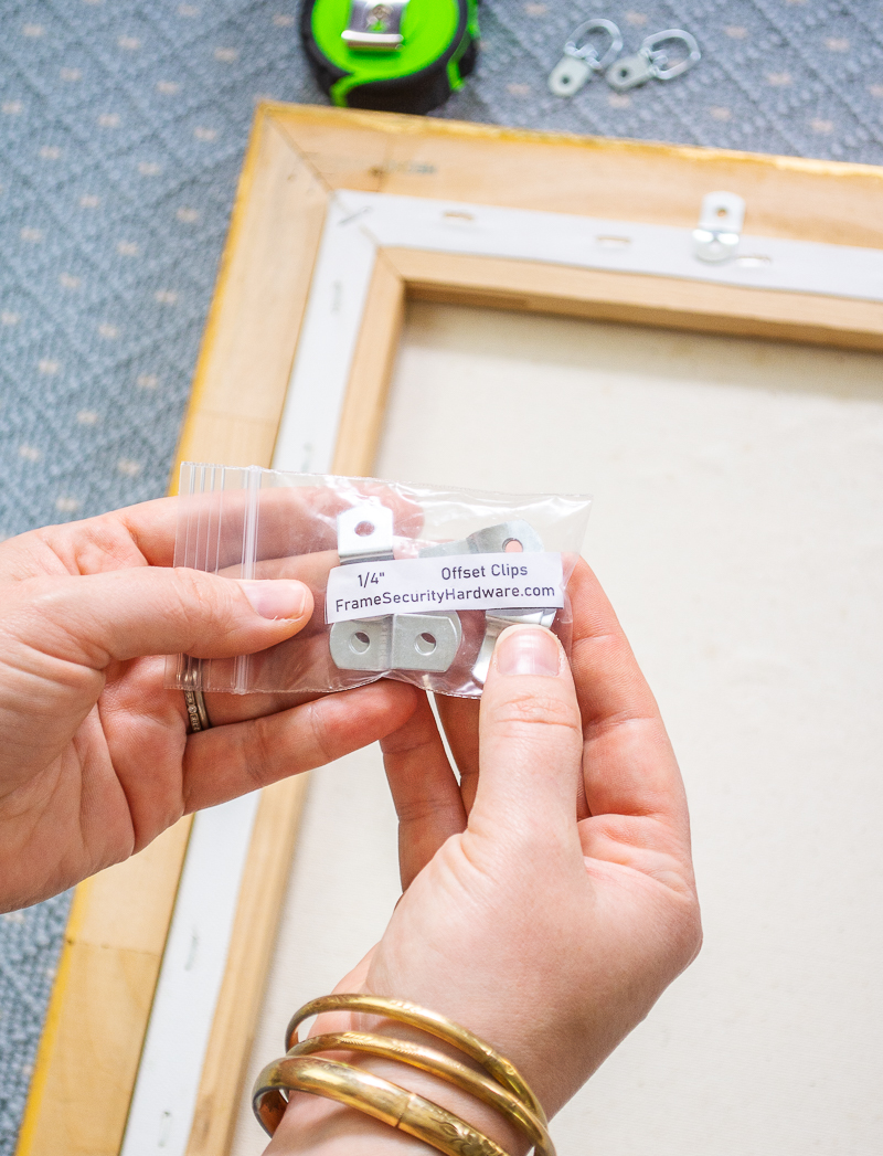 Katherine holds up packet of offset clips to use when framing a painting