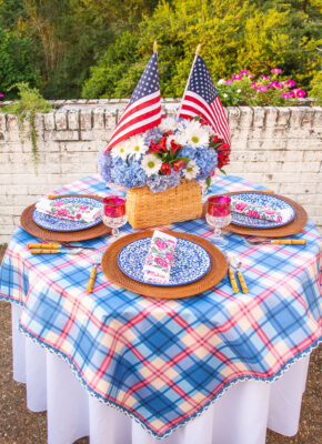 Independence day tablescape with plaid tablecloth, basket centerpiece with hydrangea and flags, splatterware dishes, and block print napkins