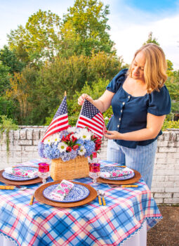 Katherine fixes American flag in floral centerpiece for Independence Day table