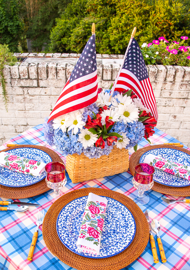 Basket centerpiece with American flags, daisies, blue hydrangea, and red Inca lilies