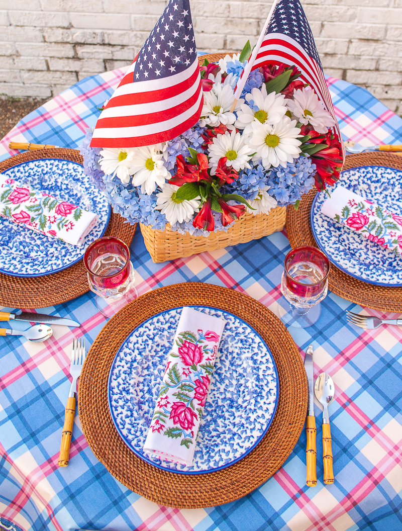 Top view of 4th of July BBQ made easy tablescape with plaid tablecloth, daisy and hydrangea centerpiece, and spongeware dishes