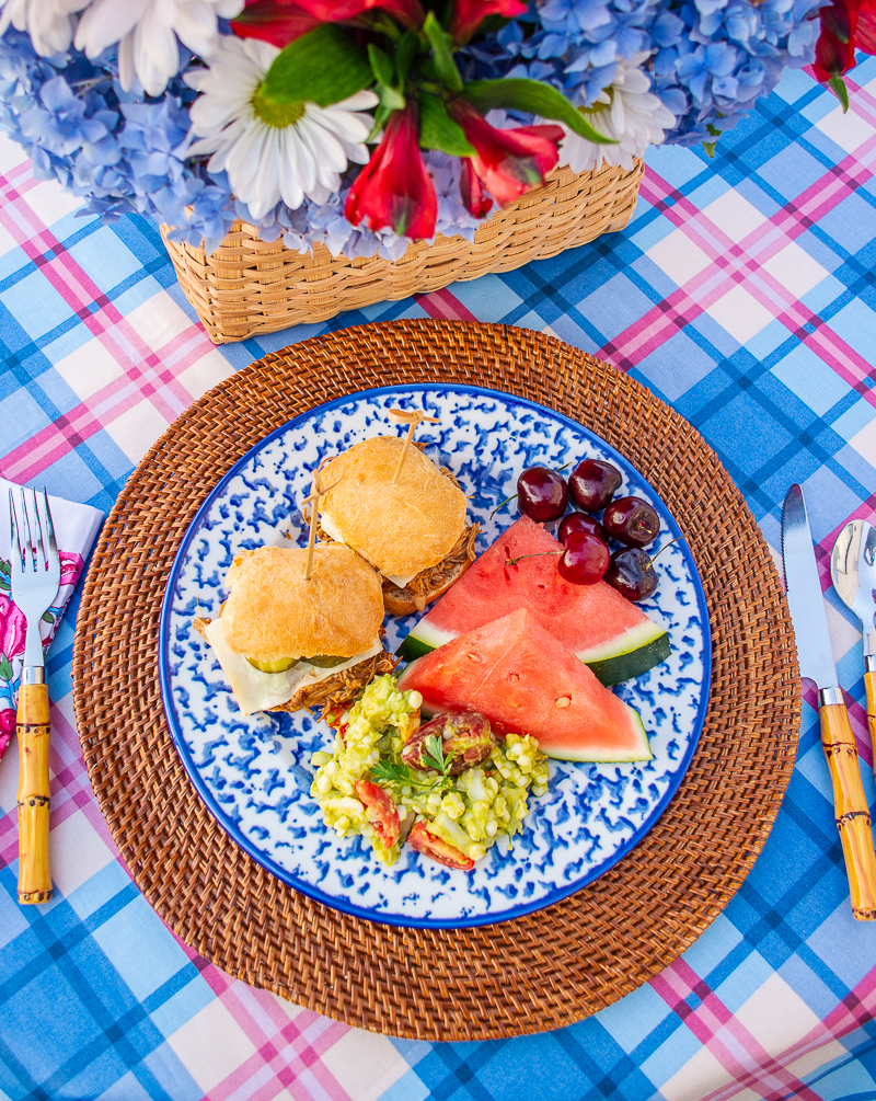 Spongeware plate filled with BBQ chicken sliders, corn and avocado salad, and watermelon - menu for 4th of July BBQ Made Easy